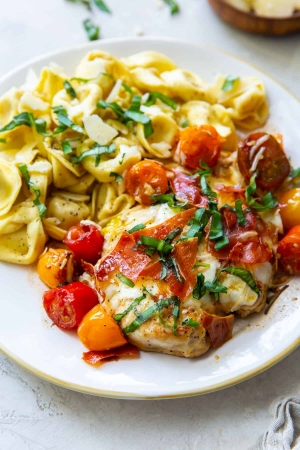 Chicken Caprese on a white plate with tortellini.