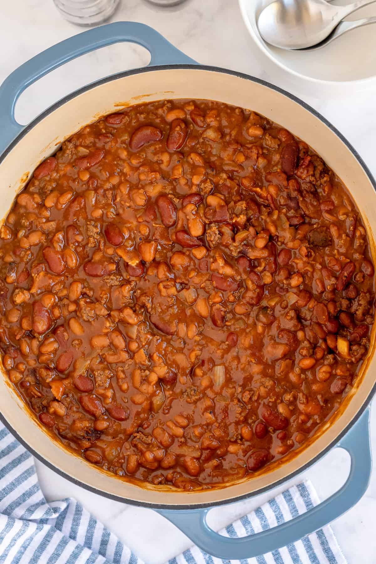 A blue Dutch oven filled with baked beans shot from over the top.