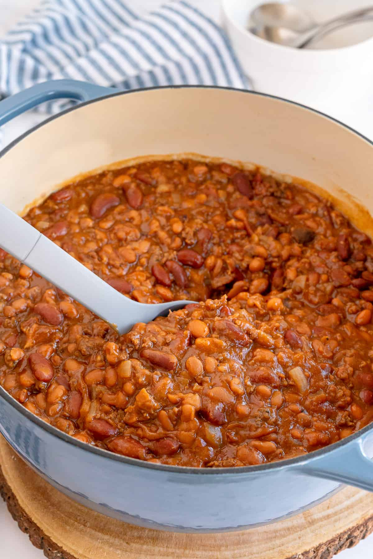 A spoon stirring baked beans in a Dutch oven.