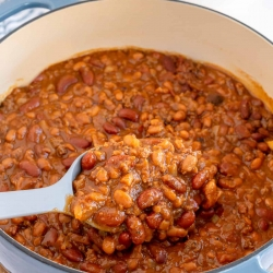 A spoon scoops baked beans from a Dutch oven.