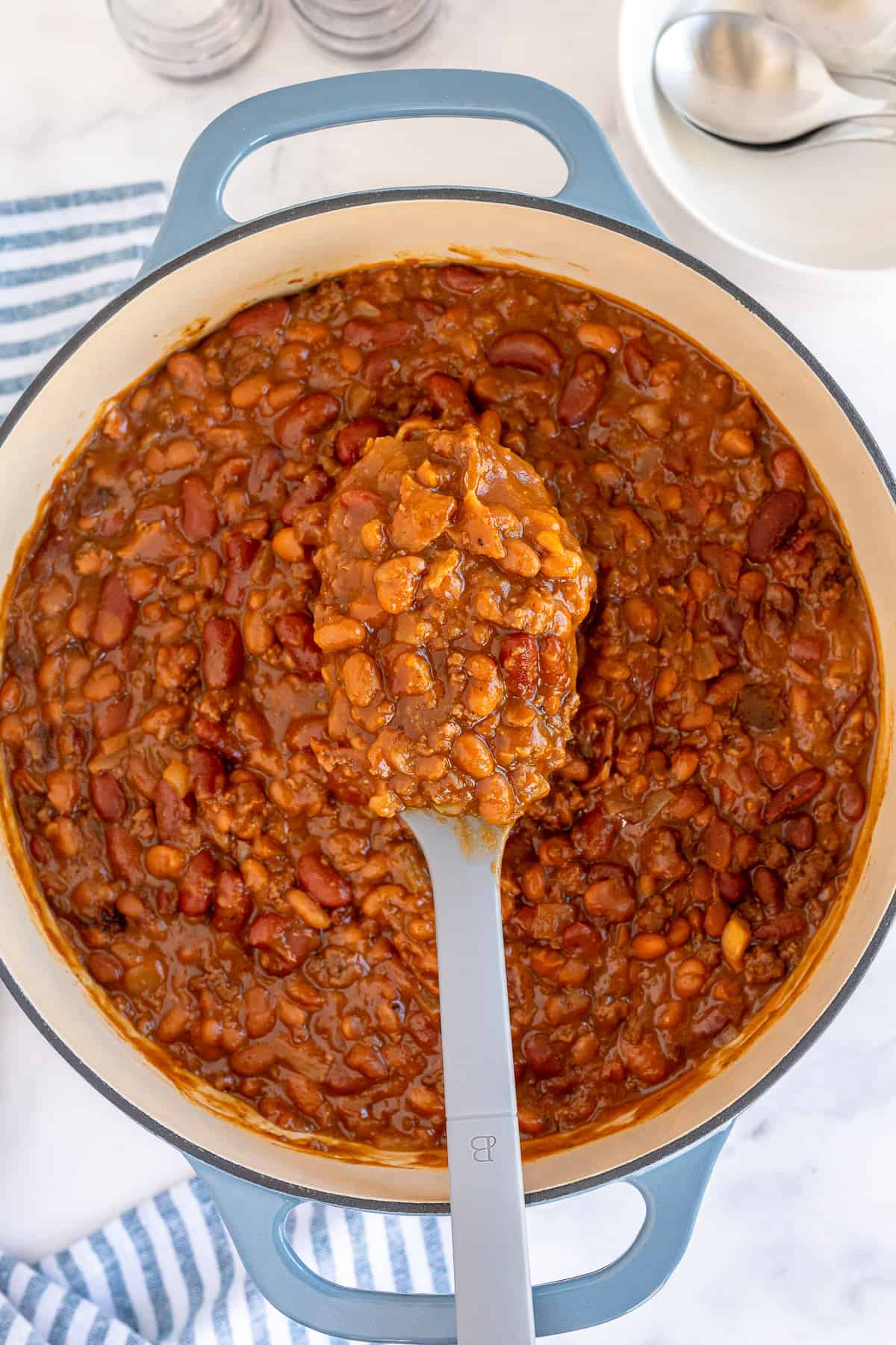 A spoon full of baked beans hovers over a pot.