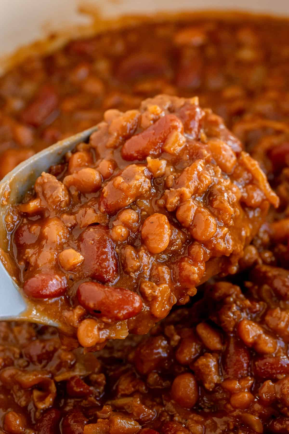 A close up of a spoon scooping baked beans.
