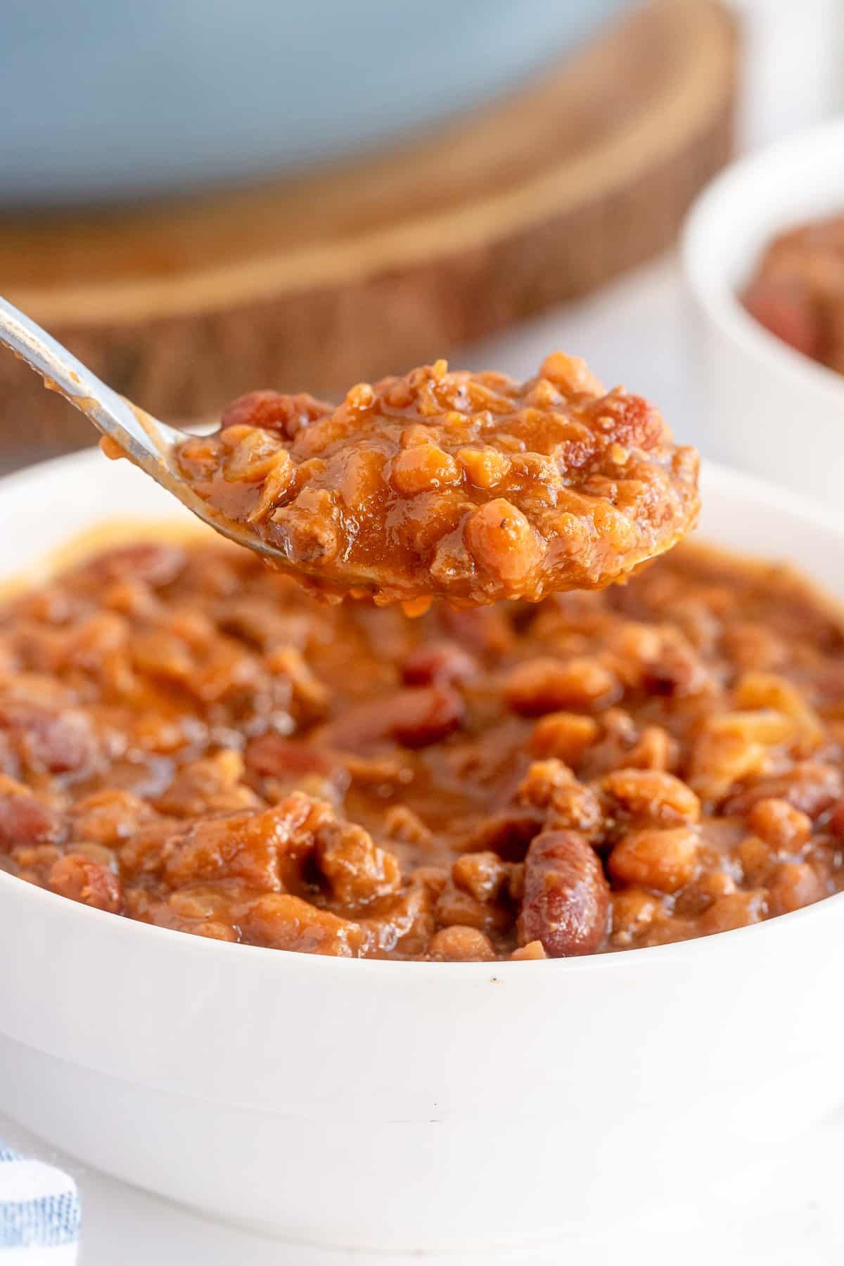 A spoon hovers over a bowl of baked beans.
