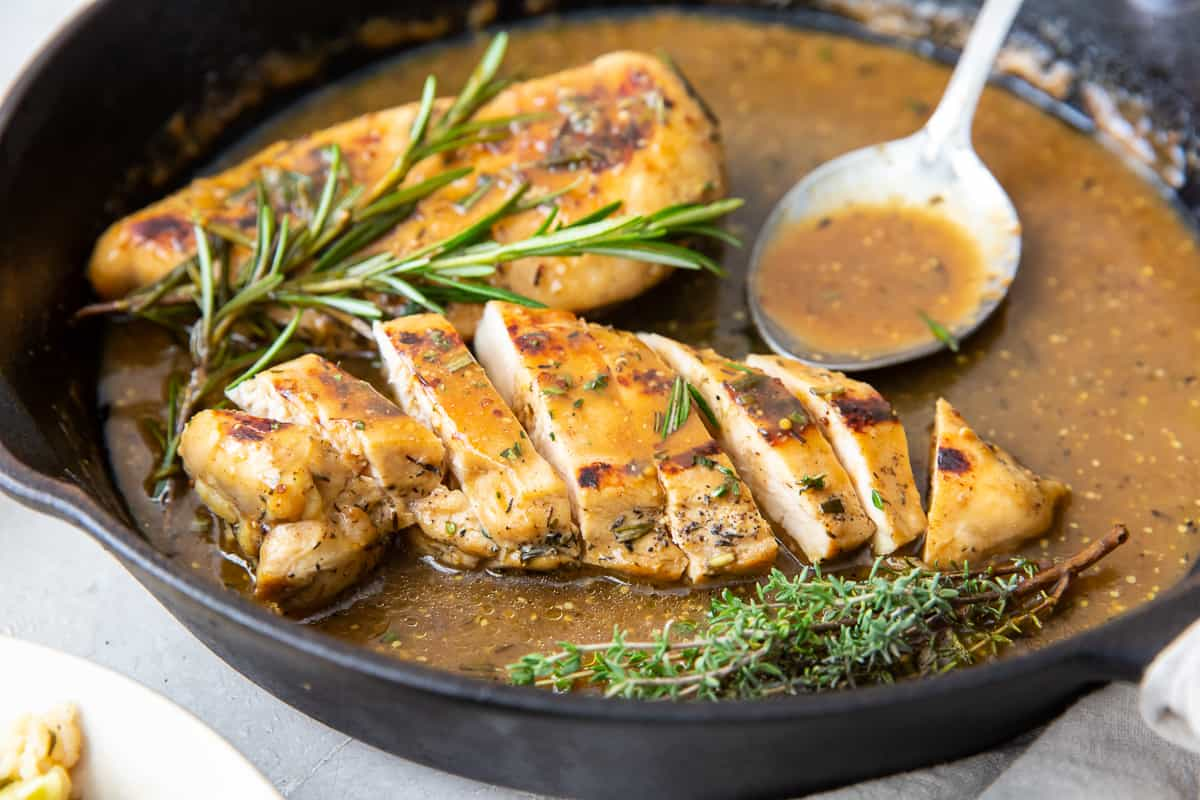 Slice chicken with apple sauce in a cast iron skillet with a spoon.