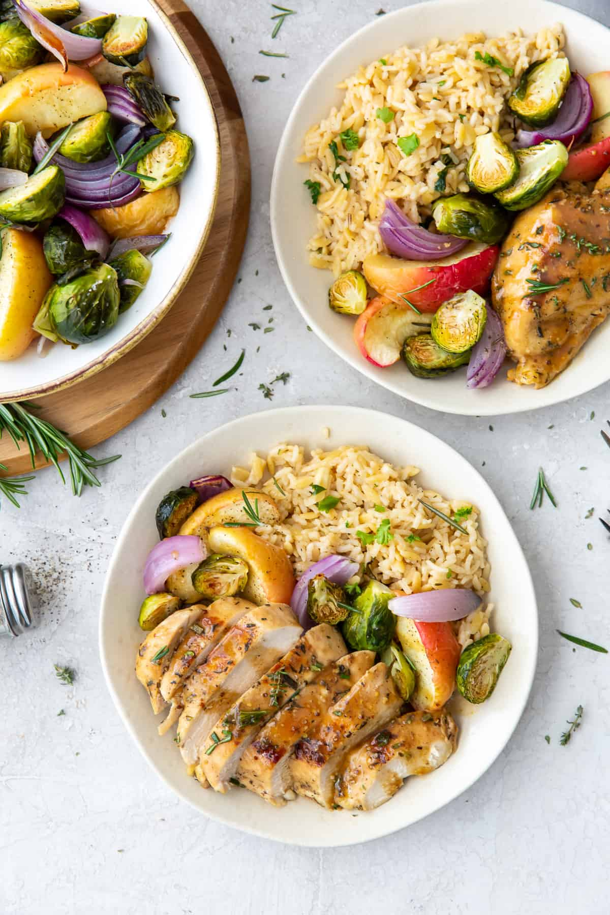 Photo over top of two bowls of apple chicken next to a bowl of roasted vegetables.