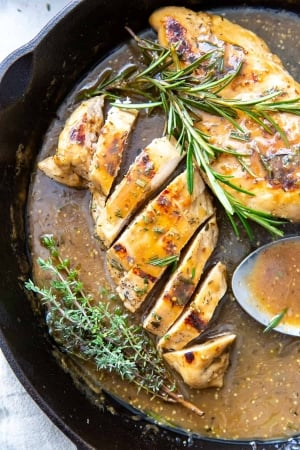 Sliced chicken and a whole breast in apple cider sauce in a skillet.