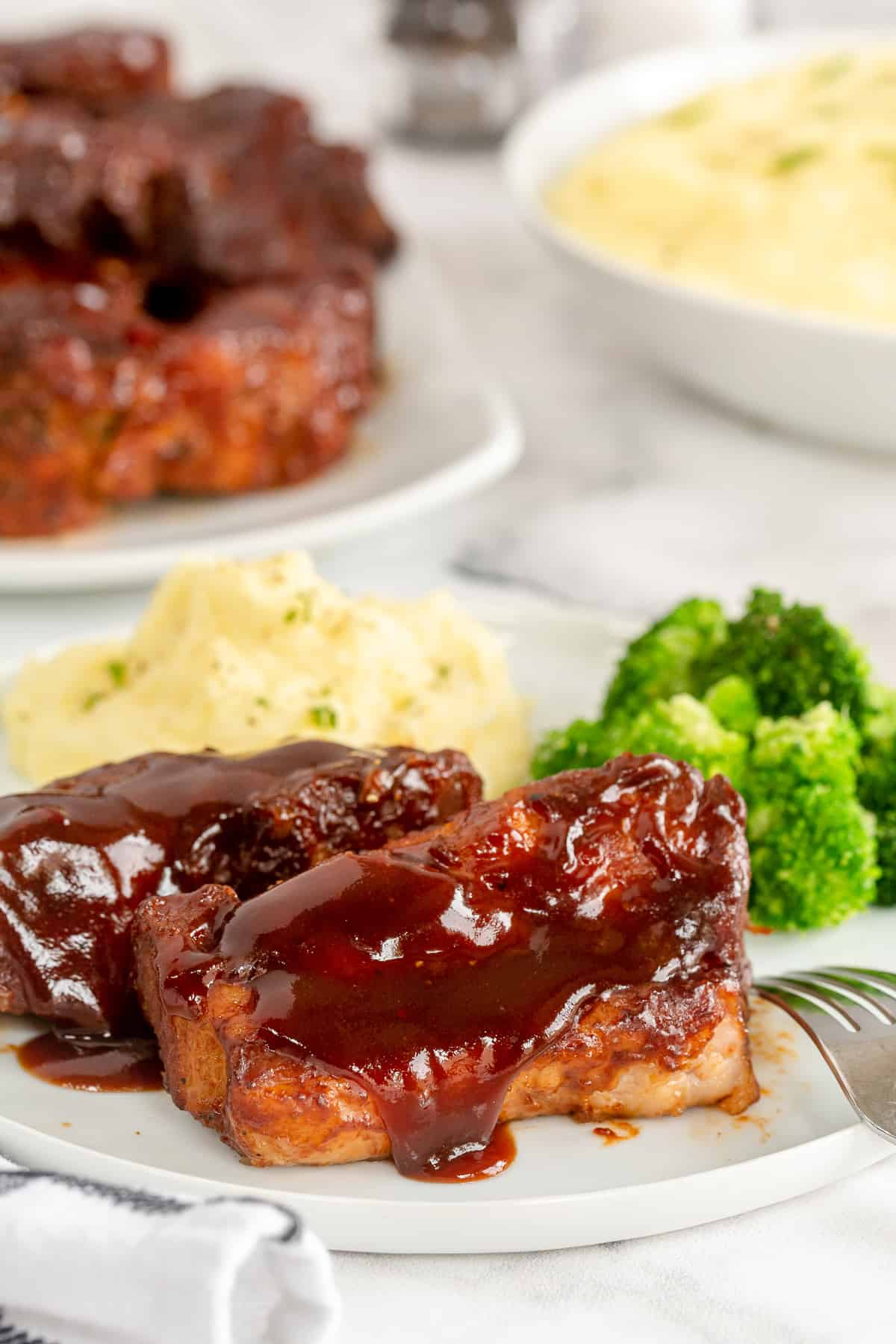 Country style ribs on a plate with mashed potatoes and broccoli.