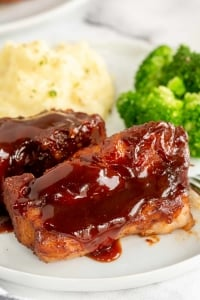 Two country style ribs with bbq sauce on a plate with mashed potatoes and broccoli.
