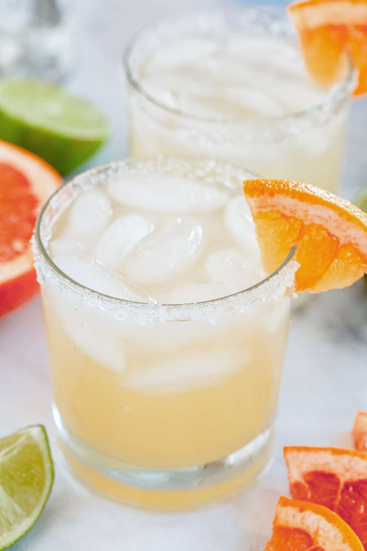 A close up of a paloma cocktail in a lowball glass with a grapefruit garnish.
