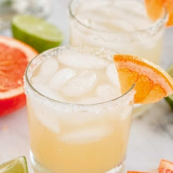 A paloma cocktail in a small glass with a grapefruit wedge on the rim.