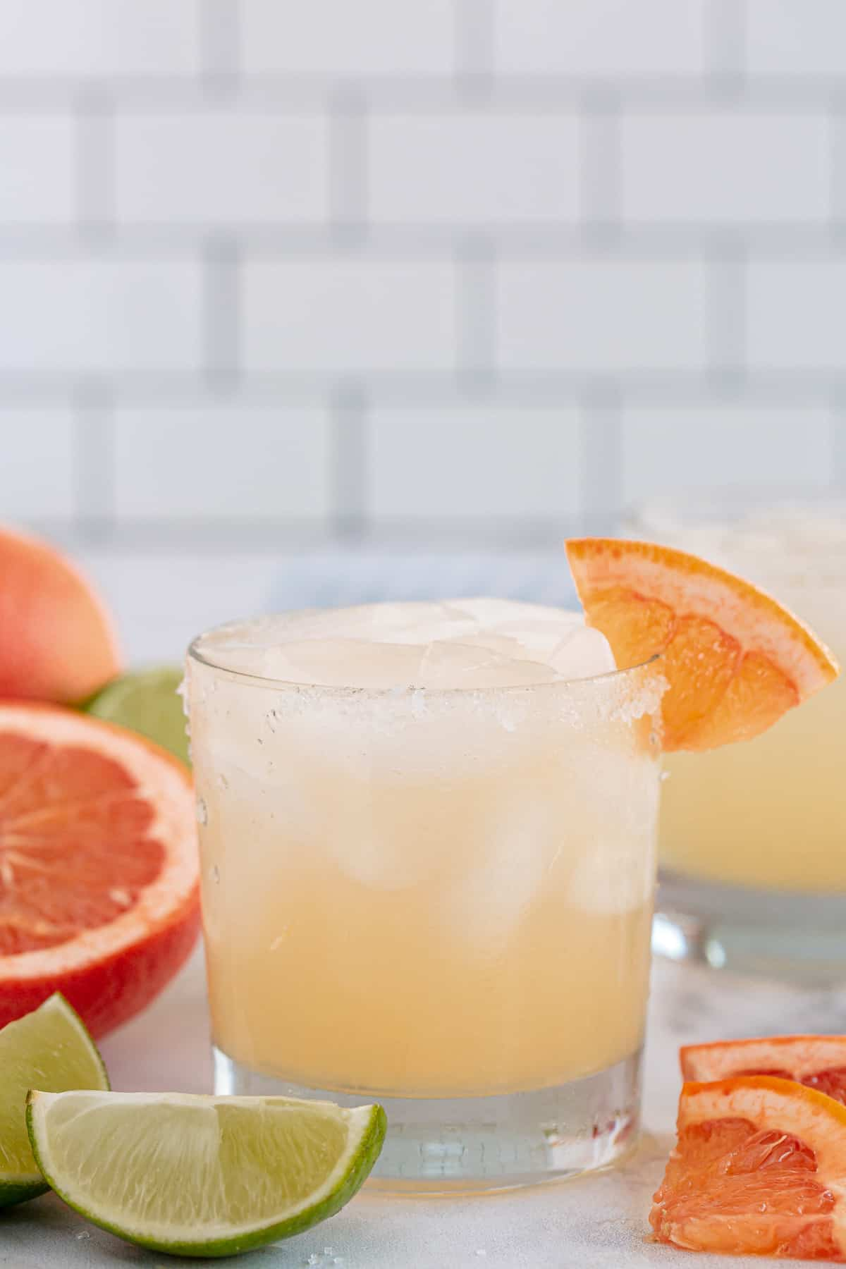 A paloma cocktail on a kitchen counter with grapefruit and lime wedges.