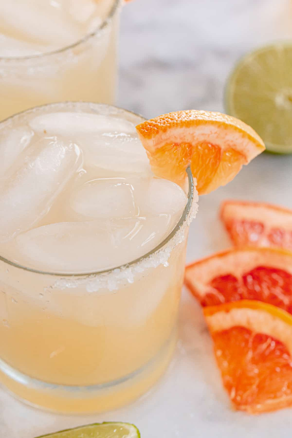 An angled top down shot of a paloma cocktail with a grapefruit garnish.