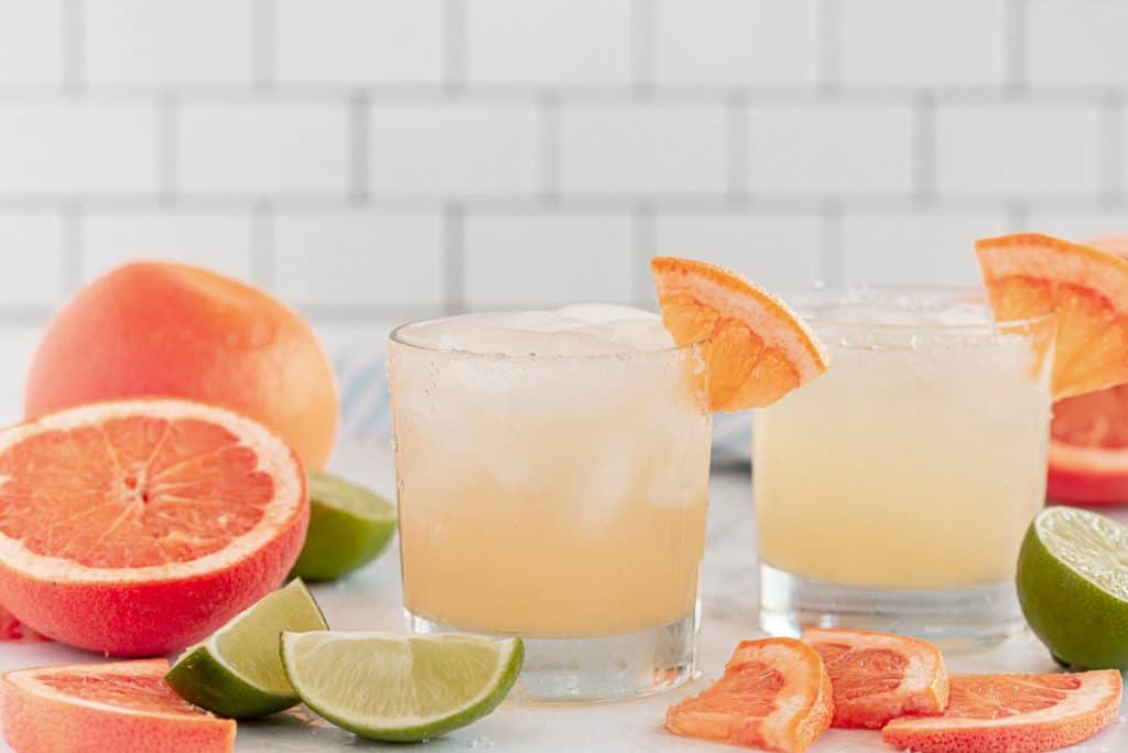Two paloma cocktails with grapefruits and limes around them.