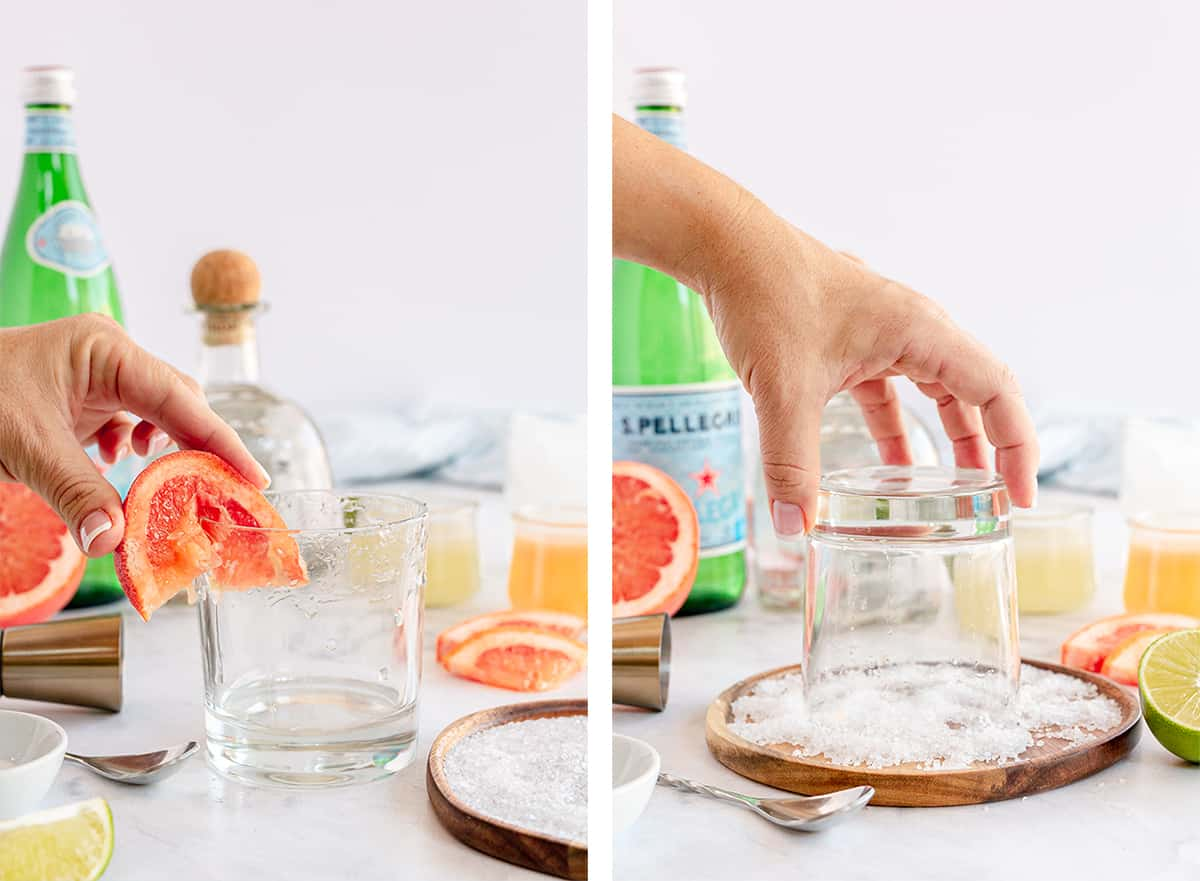 A hand rubs a grapefruit wedge around a glass rim and dips it in salt.
