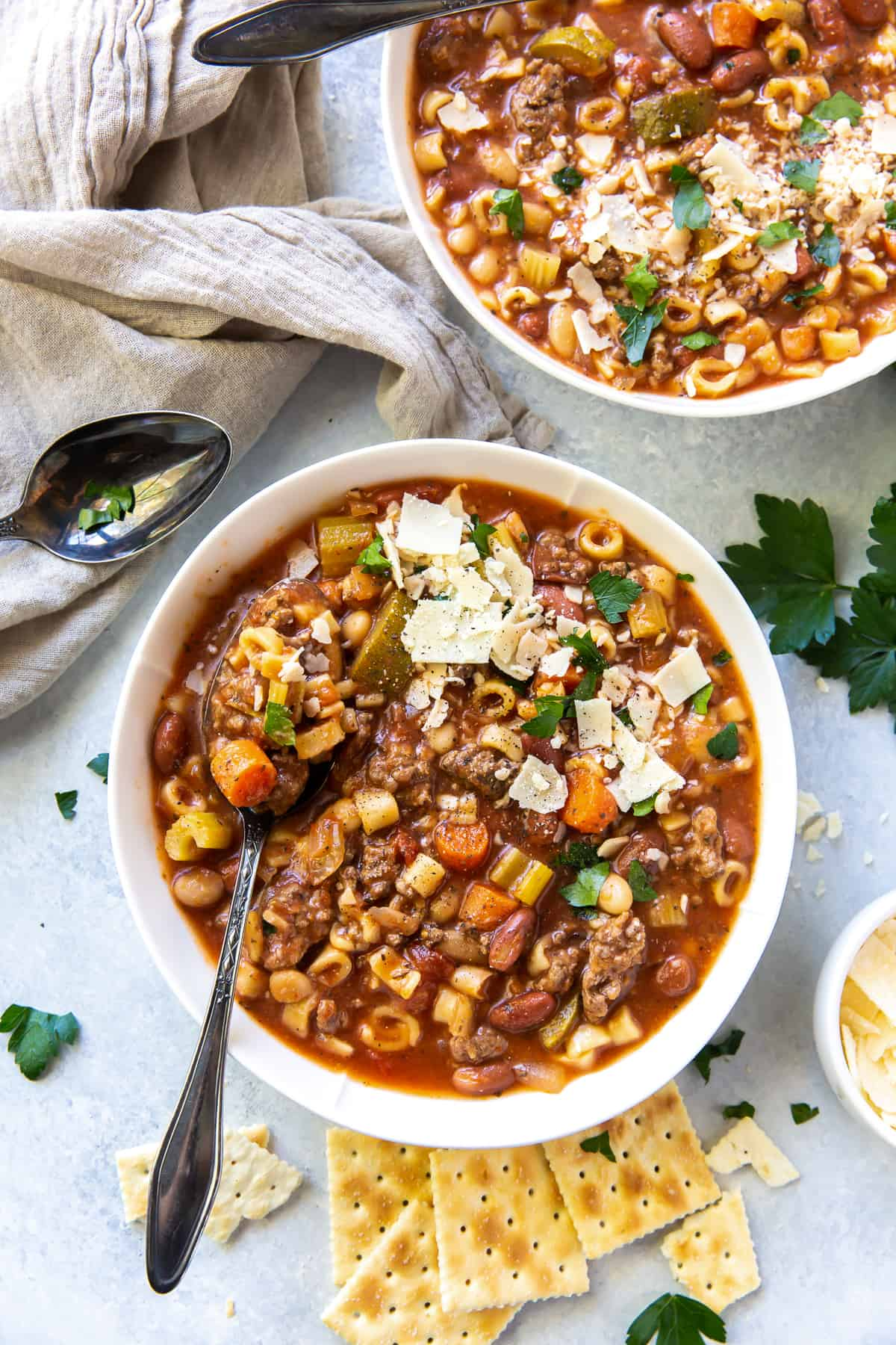 An over the top shot of two bowls of Hamburger Minestrone topped with Parmesan.