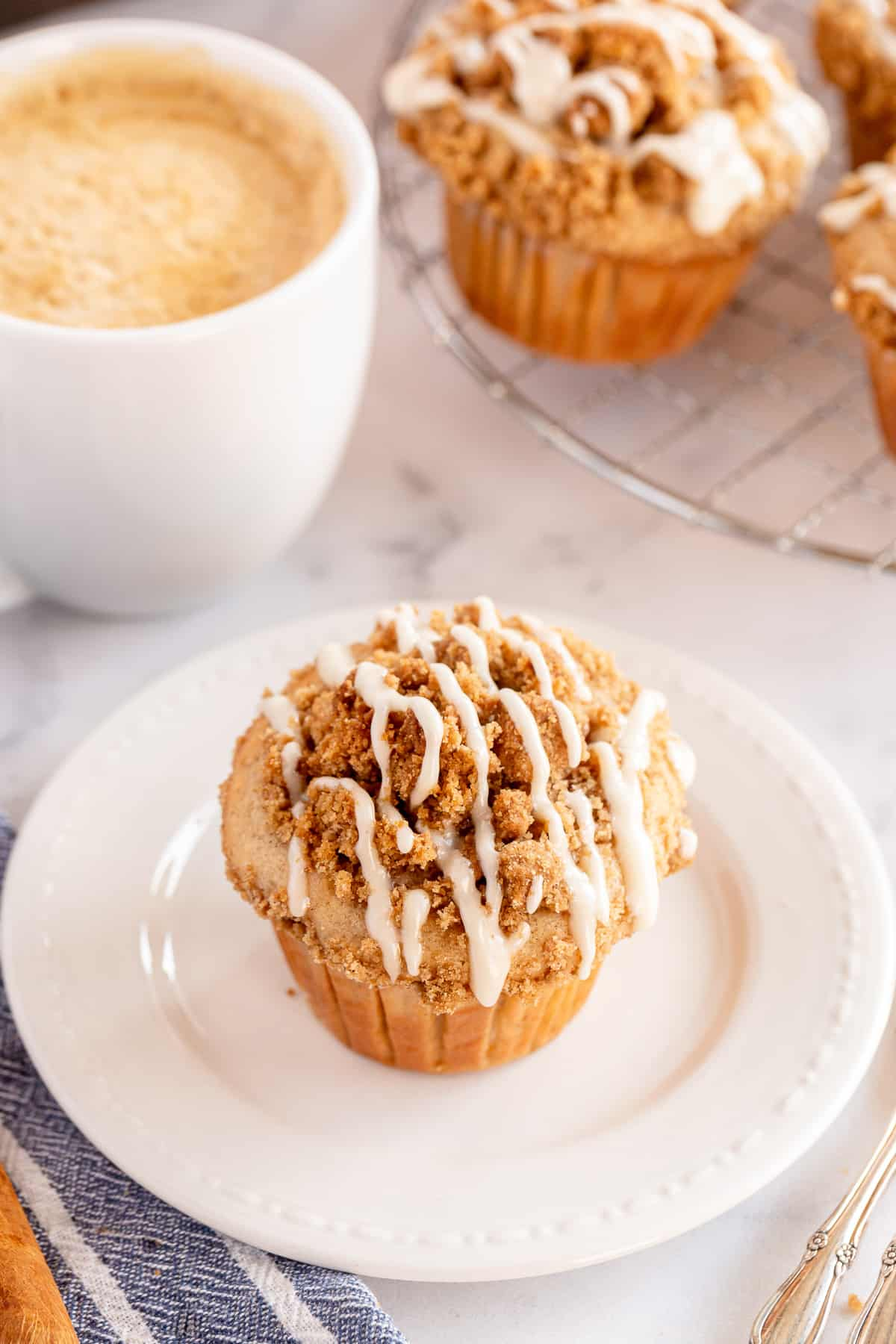 A glazed apple muffin on a white plate next to a cup of coffee.