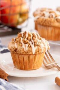 An apple muffin on a white plate in front of a crate of apples.
