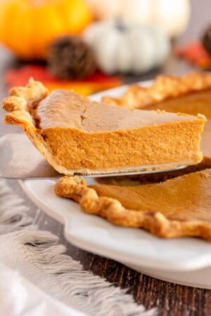 A slice of pumpkin pie being lifted from a pie plate with a spatula.