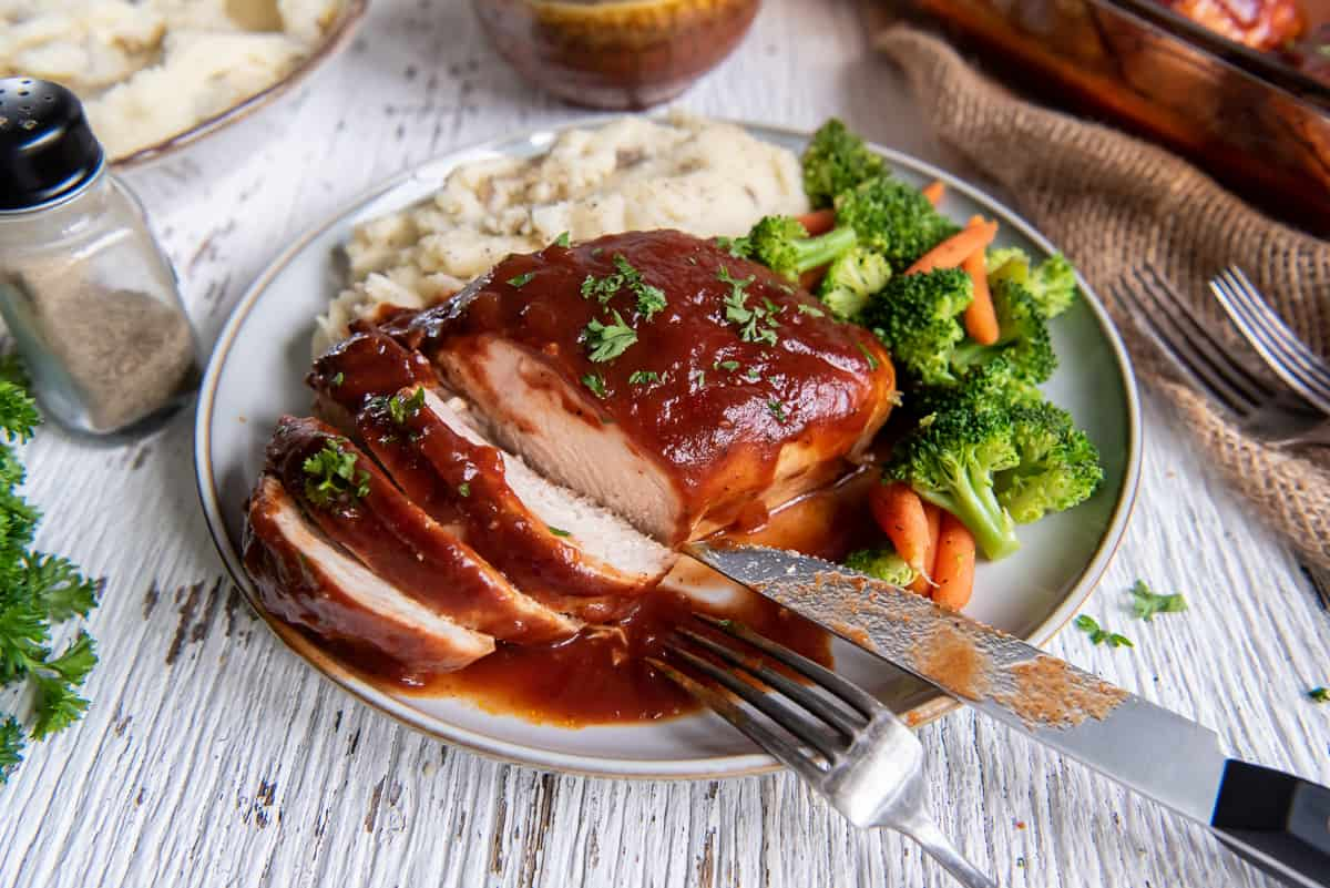 Sliced BBQ chicken on a plate with broccoli and mashed potatoes.