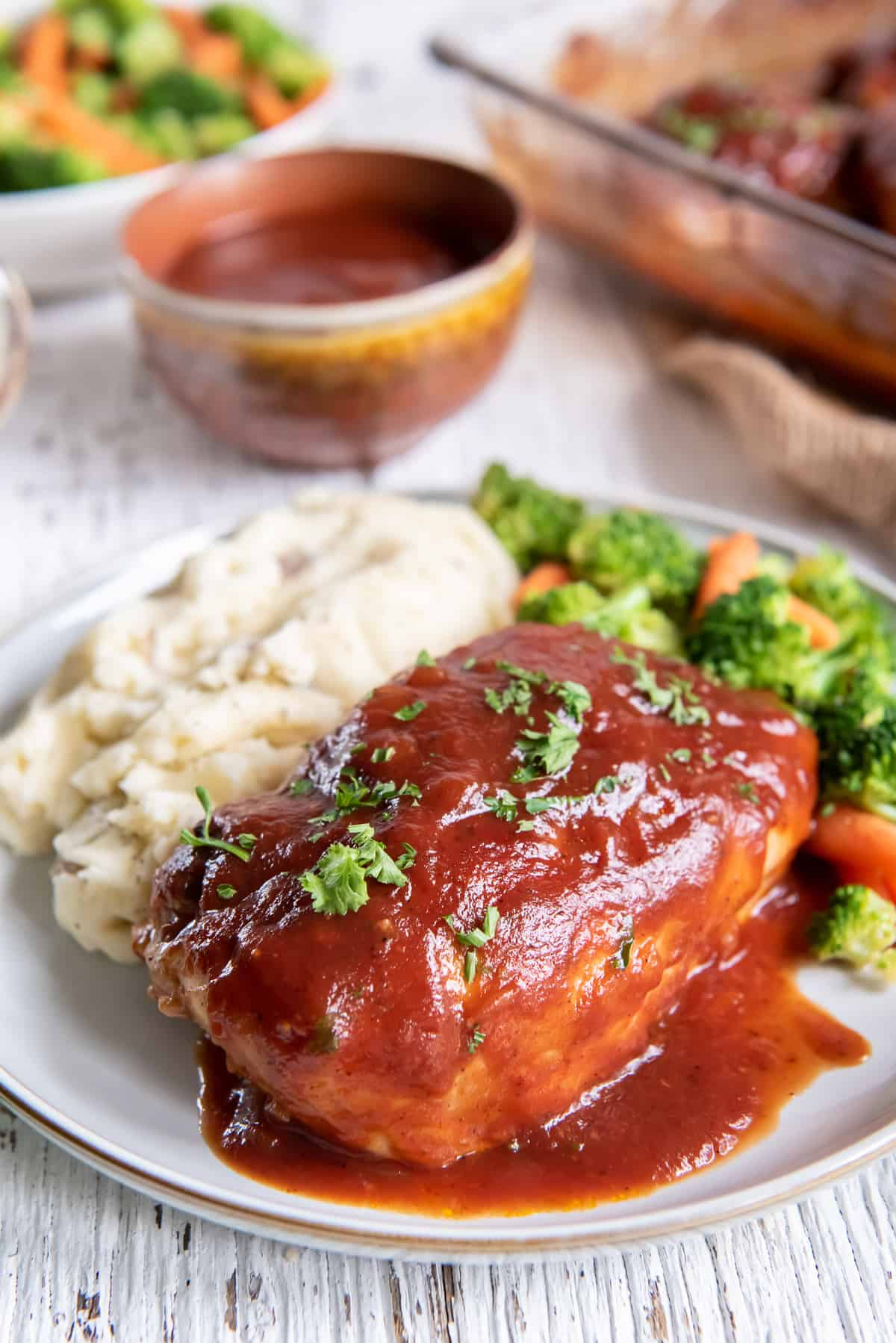 A piece of chicken topped with BBQ sauce on a dinner plate.