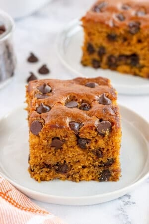 A slice of pumpkin chocolate chip cake on a white plate.