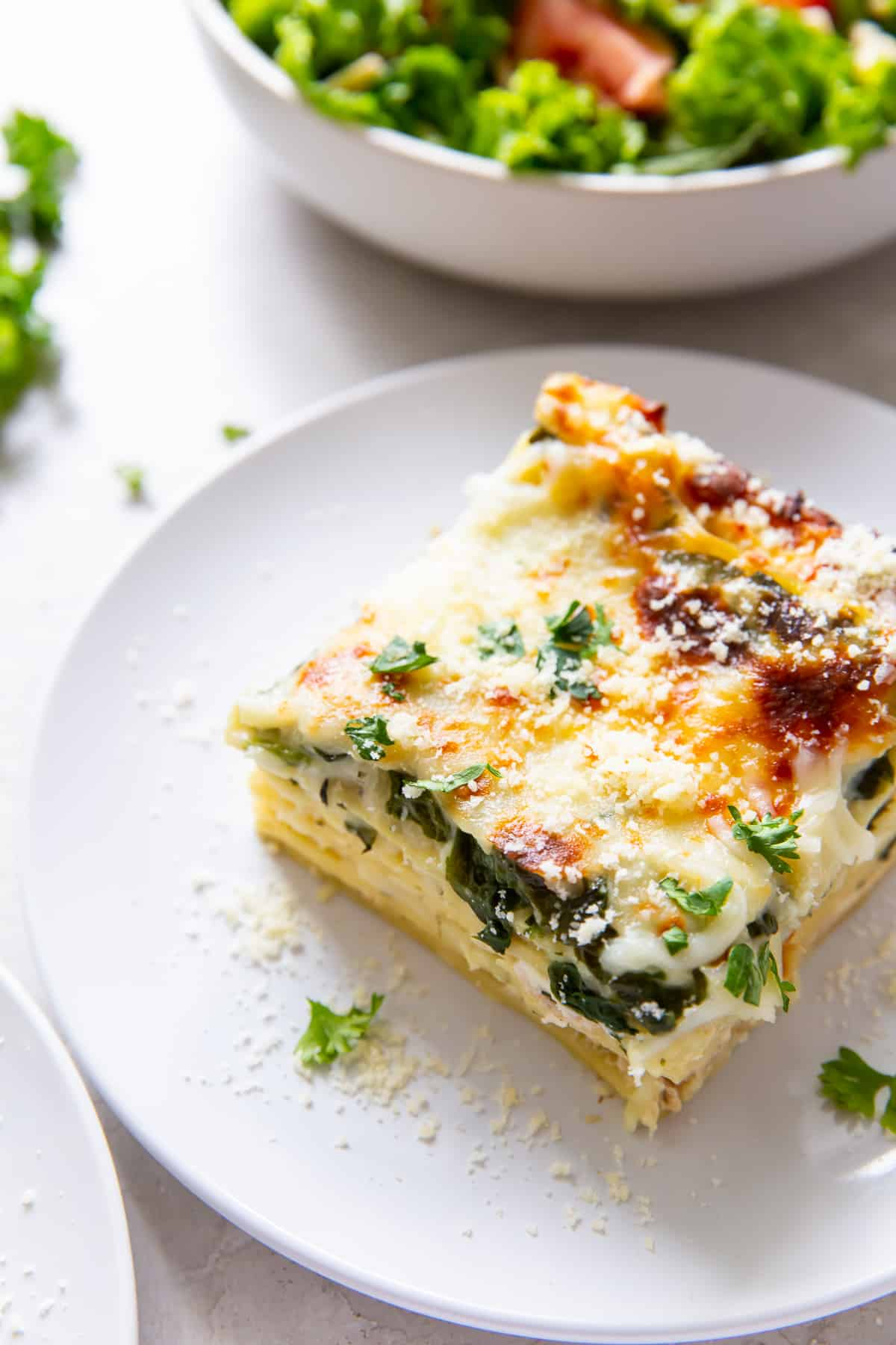 A slice on lasagna on a white plate in front of a bowl of salad.